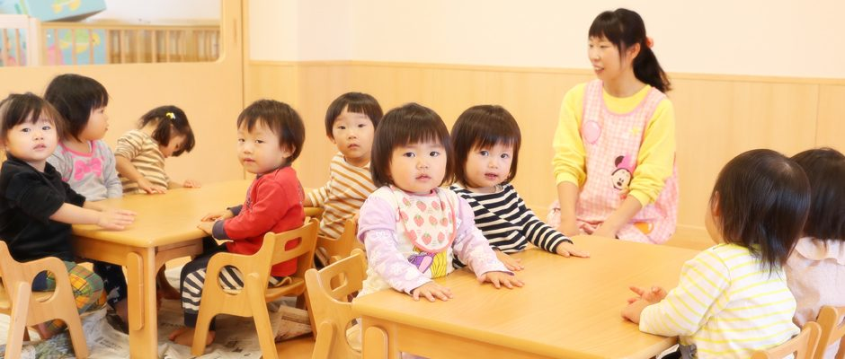 机に座る子どもたち